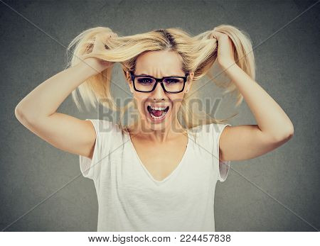 Angry woman screaming out loud and pulling her hair out isolated on gray background
