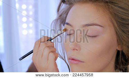 Professional make-up artist applying cream base eyeshadow primer to model eye. Beauty, makeup and fashion concept
