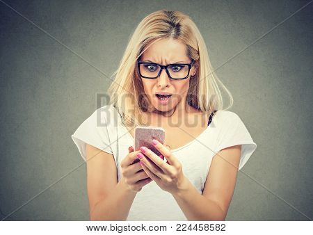 Shocked woman looking at mobile phone isolated on gray background