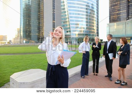 Close up face blonde secretary looking at camera and smiling with blue case in   and talking partners background. Concept of office assistant with documents outside and business employees. Beautiful blonde girl with casual make up and cute smile.