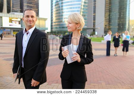 Business colleagues walking and talking after conference in La Defense Paris with tablet and case in hands,  . Concept of successful team members and speaking about work ideas. People in suits passing and smiling.
