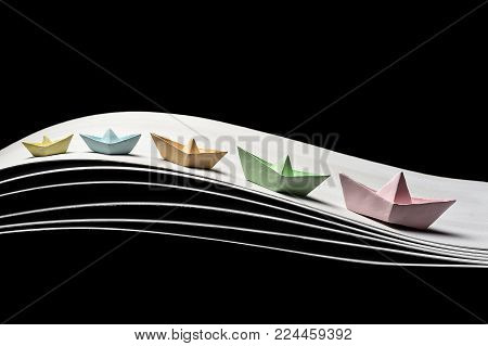 a team of five color paper boats in the dynamics on the waves and on a black background. 5 ships of different sizes