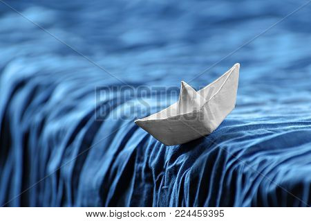 White paper boat in the dynamics on the waves and on a blue wave. White ship on waterfall