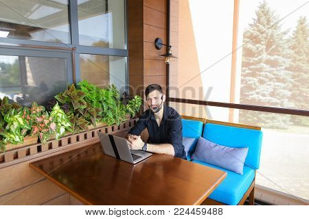 Educational consultant talking to student by laptop video call with headset microphone. Handsome serious man has beard and wears black shirt. Concept of assisting students in making decisions and giving advices in tuition fees, visa