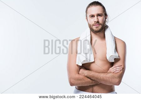 Cheerful caucasian man with bath towel around his neck looking at camera with arms crossed, isolated on white