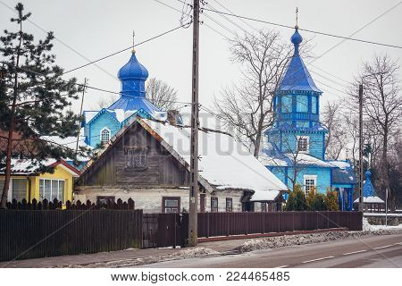 Houses and Exaltation of Holy Cross wooden Orthodox church in Narew, small village in Podlasie region of Poland