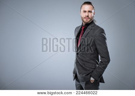 Businessman in formal suit looking at camera with hands in pocket, isolated on gray