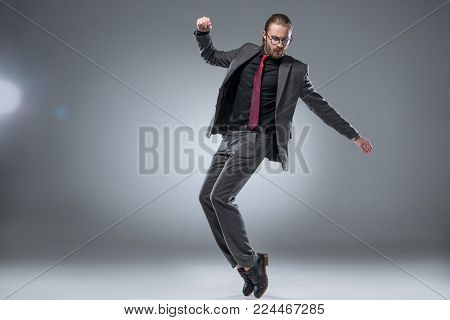 Seruous businessman in glasses in formal suit about to jump with hands outstretched while looking down, isolated on gray