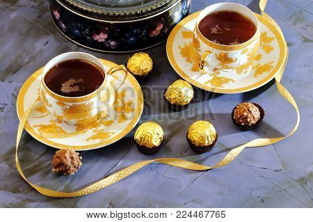Tea ceremony, tea party. Two tea cups of gold color with black tea, candy, chocolate and a box with cookies on a lilac-colored background.
