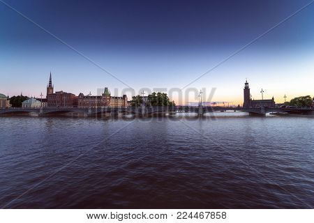 Magnificent sunset in Stockholm. Dark water and iridescent skyline. Panoramic view of the Stockholm City Hall, city center and the bridge.