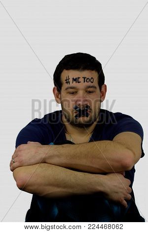 Person of young man with the inscription `me too`.Young man with the inscription on his forehead and with black adhesive tape on mouth.