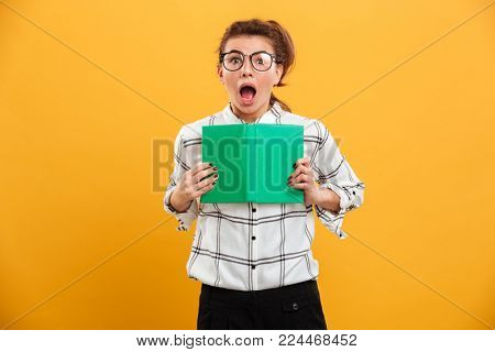 Portrait of excited woman involved in reading fascinating book holding in hands isolated over yellow background