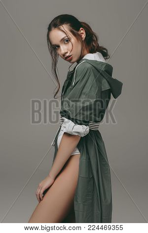 beautiful stylish girl posing in green raincoat, isolated on grey