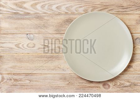 empty matte round plate on wood table. top view.