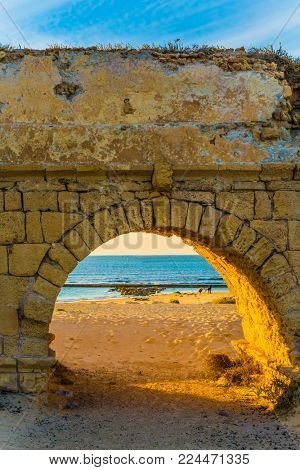 Stunning sunset on the Mediterranean coast in Israel. Well-preserved aqueduct, built in Caesarea at the beginning of the Byzantine period. Concept of ecological and historical tourism