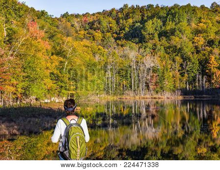 Woman -  tourist with a green backpack admires the beautiful lake. Magnificent resort in French Canada - Mont Tremblant. Concept of ecological and active tourism