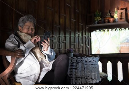 asian elder woman holding mobile phone on terrace. elderly female texting message, using app with smartphone on balcony. senior use cellphone to connect with social network