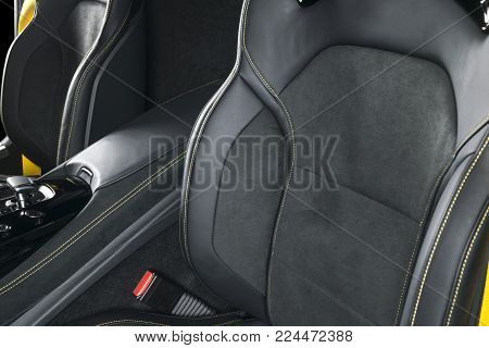Modern Luxury car inside. Interior of prestige modern car. Comfortable leather seats. Black perforated leather with yellow stitching. Steering wheel and dashboard. automatic gear stick shift.
