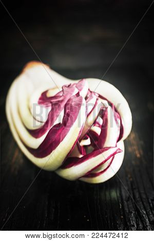 Radicchio of Treviso red chicory on old black board.