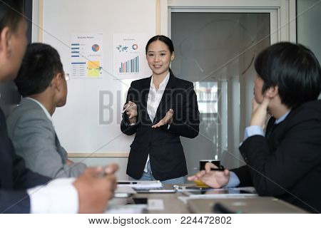 Businesswoman Present Financial Plan Report To Co Worker Team. Woman Leader  Discuss Sales Data With
