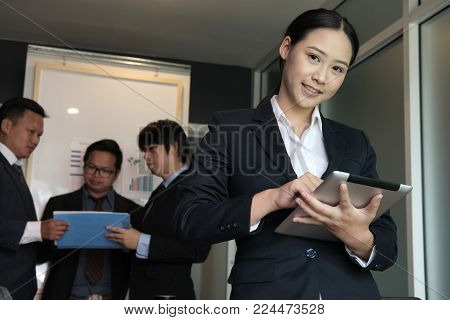 businesswoman smile at business meeting. young woman working on touchpad at office. female freelancer hold digital tablet in her arms at conference