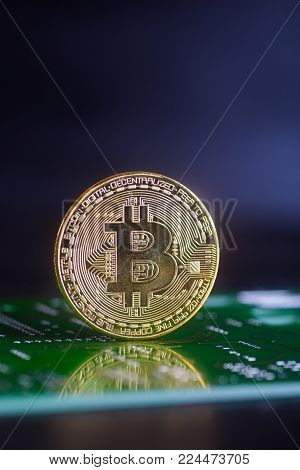 Golden Bitcoin On Green Board With Microchips And Microcircuits On Background.