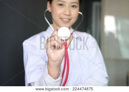 Female Doctor Showing Stethoscope For Checkup At Clinic. Physician Or Medical Practitioner Holding S