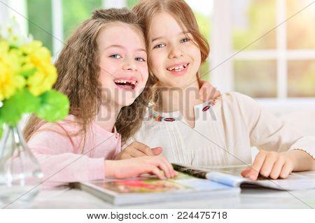 Portrait of two little girls reading magazine