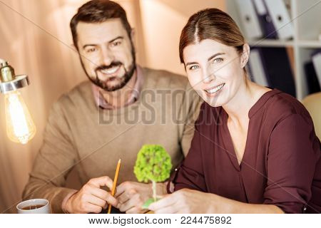 Friendly colleagues. Attractive woman keeping smile on her face and turning head while looking at camera