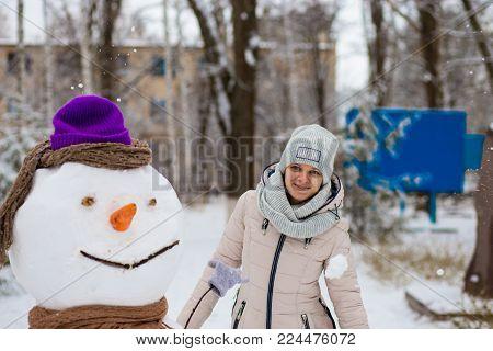 Stylish woman sculpt a big real snowman. Beautiful woman has fun in winter park, wintertime