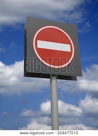 Circular Red And White Road Traffic No Entry Sign Against Blue Sky Background