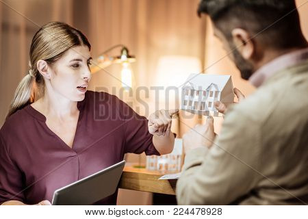 Study information. Serious young woman holding tablet and turning head while looking at little house