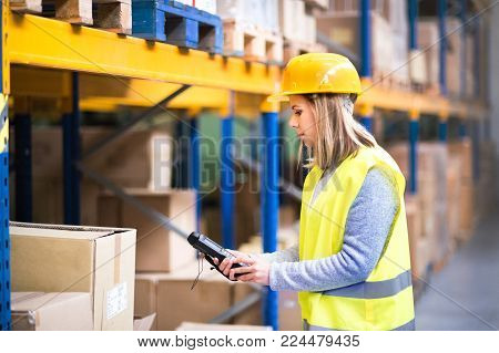 Warehouse woman worker or supervisor with barcode scanner. A mobile handheld PC with barcode scanner.