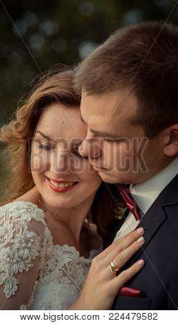Close-up sensitive wedding portrait of the pretty smiling newlyweds softly hugging
