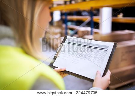 Young woman warehouse worker or a supervisor controlling stock.