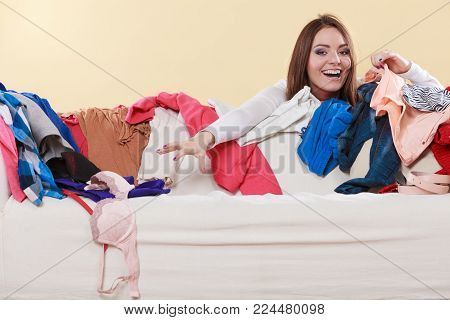 Happy woman picking clothes up off sofa couch in messy living room. Young girl surrounded by many stack of clothing. Disorder and mess at home.