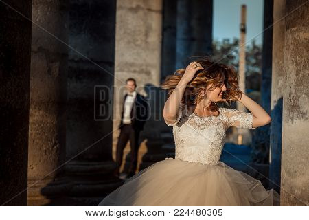 Emotional portrait of the beautiful attractive bride shaking and touching her ginger curly hair at the blurred background of the doom near old castle during the sunset