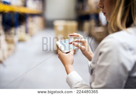 Unrecognizable woman warehouse worker or supervisor with smartphone.