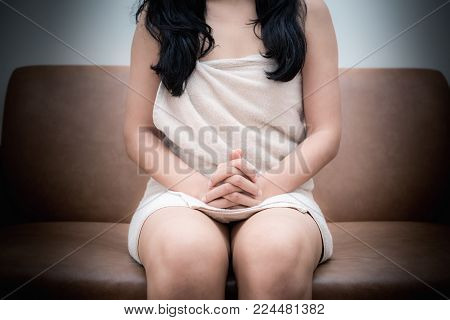 Portrait of human trafficking victim is seating at the couch.