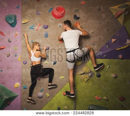Happy man and woman fitness professional climbers having training at bouldering gym. Young sportsmen climbing artificial rock wall, reaching the top and support concept