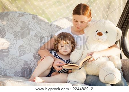 Mother And Child Reading Book Together.