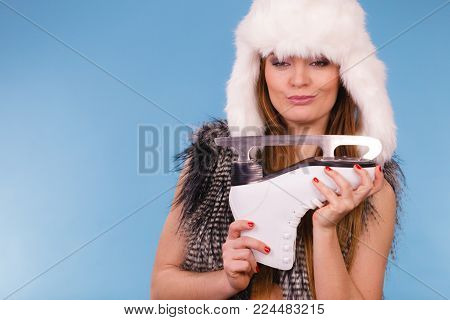Winter, sport, people concept. Attractive lady with ice skates. Young woman wearing fur cap.