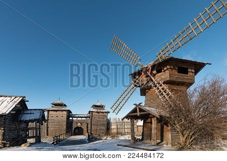 Ancient Wooden Fortress, A Mill And Log Huts. Russian Village In The Winter. Russia. Suzdal.