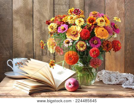 Country still life with flowers, book and Apple. Bouquet of garden flowers in a vase.