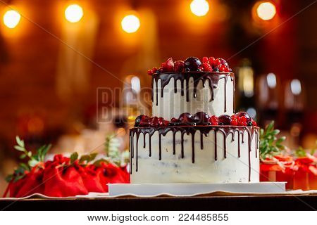 Two level white wedding cake, decorated with fresh red fruits and berries, drenched in chocolate. Bright banquet table decoration on background of lights and guests gifts.