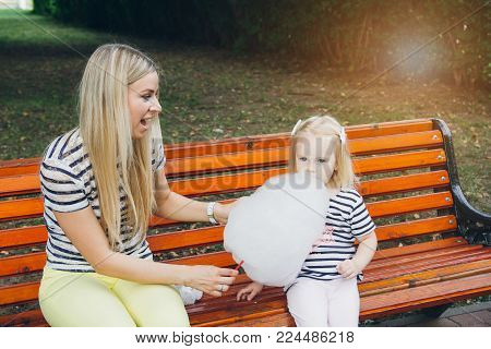 Mother And Little Daughter Eating Cotton Candy
