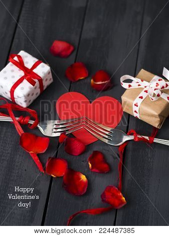 Red paper hearts and a fork with a ribbon. Dark wooden background. Copy space. St. Valentine's Day. Greeting card.