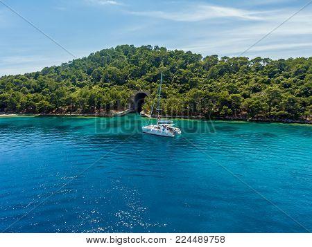 Catamaran in the background of the island. Catamaran near the island.
