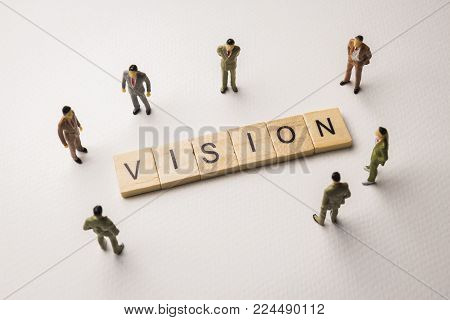 Miniature figures businessman : meeting on vision letters by wooden block word on white paper background, in concept of business and corporation
