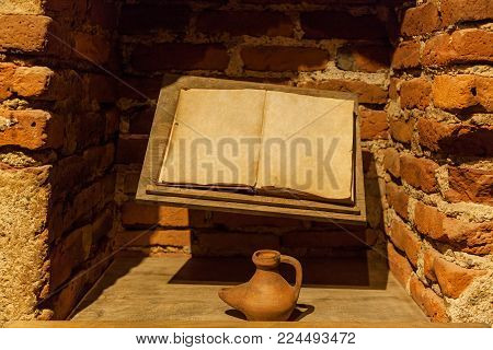 Ancient book with an inkwell near a brick wall. Ancient book with an inkwell.